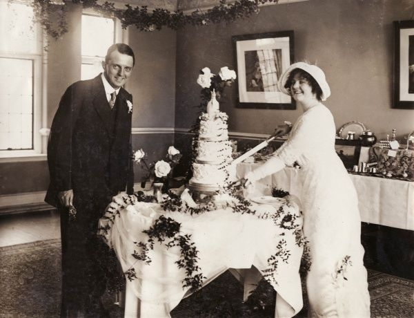 Scene at the wedding reception of Dan Everard and Dollis Brook, performers in the Pelissier Follies. The wedding took place at Finchley Parish Church, north London. Here the bride is cutting the first piece from a three-tiered cake