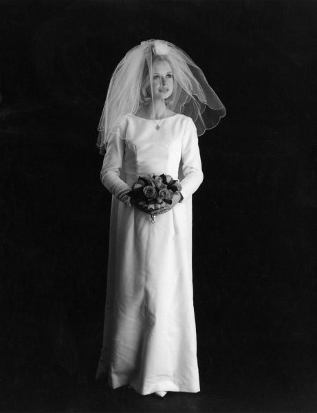 A young bride in her wedding dress wearing a veil and carrying a bouquet of roses