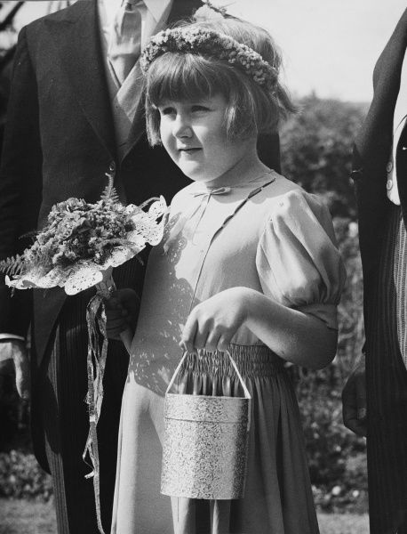 A bridesmaid has a novel wedding gas mask container decorated with silver paper at a wedding in Sidcup in Kent during World War II in 1939