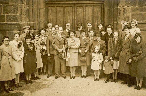 A wartime wedding group pose in front of church doors
