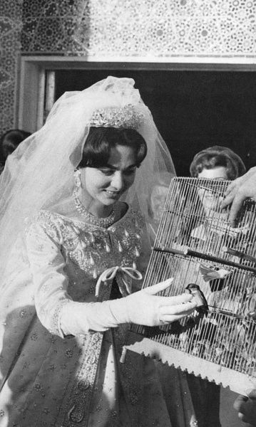 Farah Diba (born 1938), third wife of Mohammad Reza Pahlavi, last Shah of Persia (Iran), symbolically setting free some caged birds on the day of her wedding, wearing a dress by Christian Dior. Date: 1960