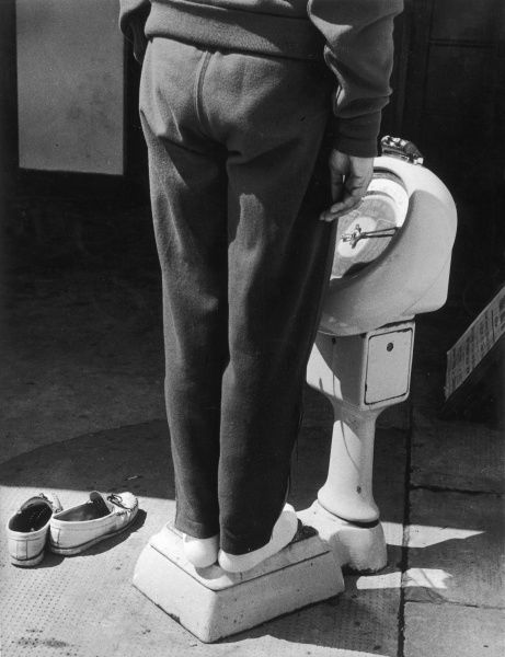 A person stands on weighing scales with their loafers placed to the side. Photograph by Heinz Zinram