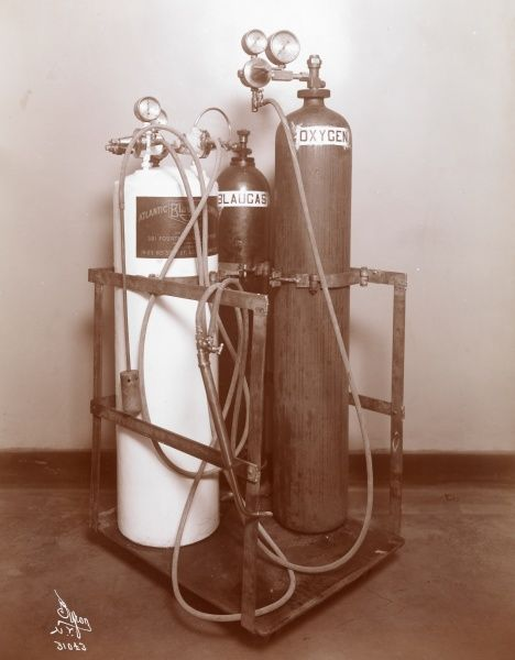 Atlantic Blaugas Co. Three compressed air tanks in a cart with labels reading Oxygen, Blaugas, and one with the Atlantic Blaugas Co. logo
