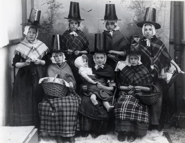 A group of seven Welsh girls in traditional costume. One of them holds a large doll on her lap, and three are holding baskets