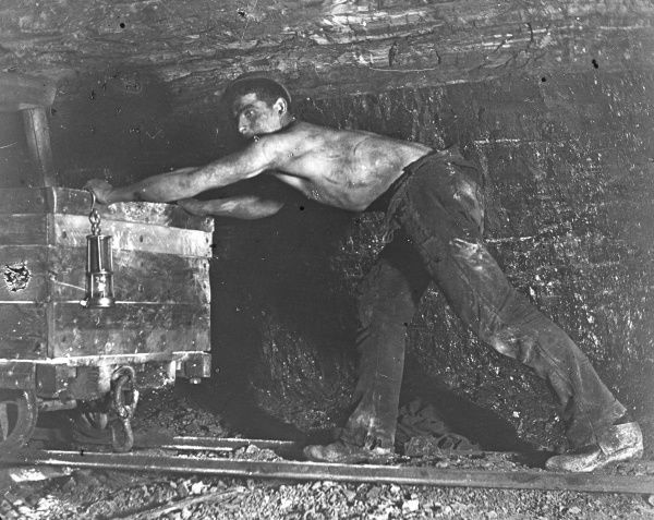 A Welsh miner, stripped to the waist, pushing a truck in a coal mine