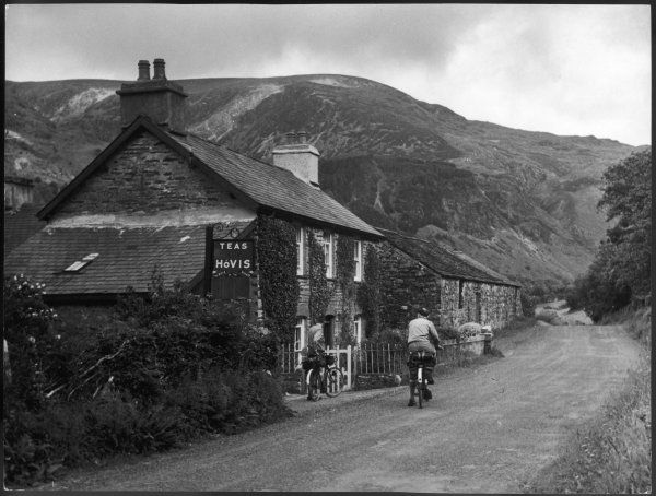 Two lucky cyclists contemplate whether or not to enter some tea rooms, which also have Hovis bread, in the mountains of Snowdonia, near Lake Tal-y- Llyn, north Wales