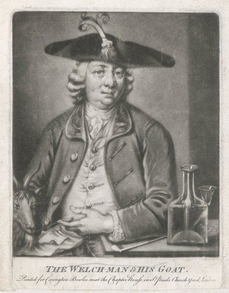 Portrait of a Welshman wearing a hat with a cocked brim trimmed with a leek. He sits with his pipe and port and his goat