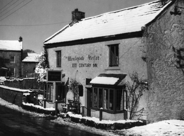 The 'Wensleydale Heifer', an inn in West Witton, Yorkshire, England, covered in winter snow. Date: 17th century