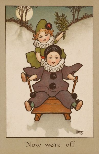 Two small children, wearing clown and Pierrot costumes have fun in the snow on a sledge