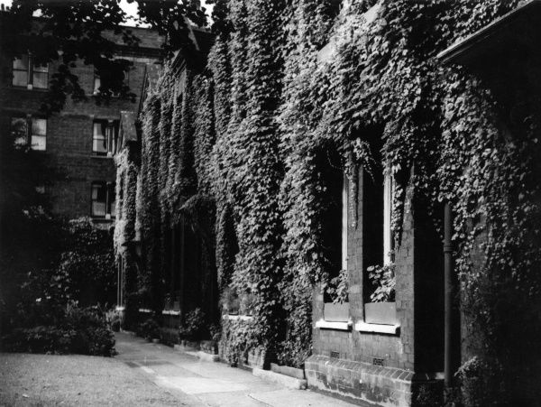 Westminster Almshouses, Rochester Row, London. A plaque on the wall reads - 'The Reverend James Palmer's Charity, founded 1656, rebuilt 1851'. Date: 1930s