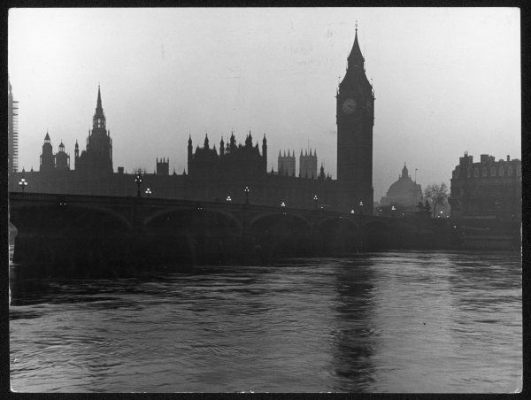 A moody photograph of the Westminster parliament buildings and the river Thames in the early evening