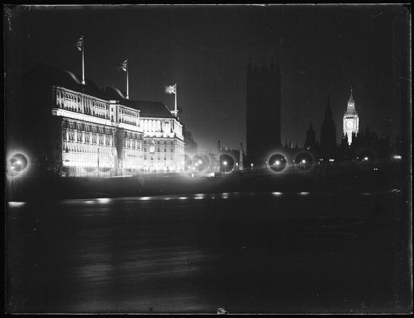 Millbank and the Houses of Parliament, Westminster, central London, floodlit at night for dramatic effect