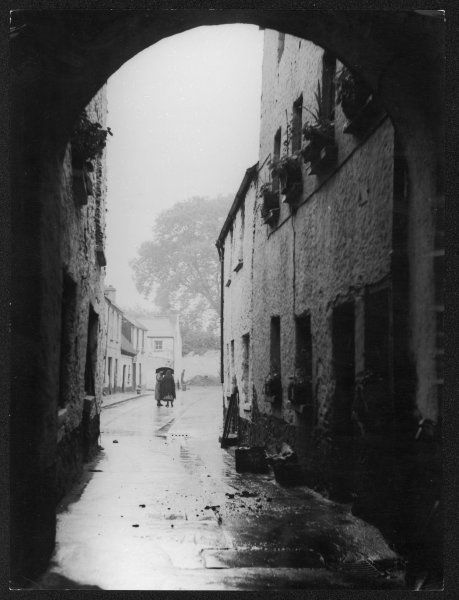 Two women pass the day of time in an otherwise empty, rainy street in Killarney, Co. Kerry