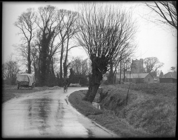 A man cycling down an English country lane during rather wet Easter weather