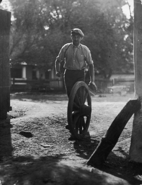 A man, possibly a wheelwright, wheels a large cart wheel across a yard