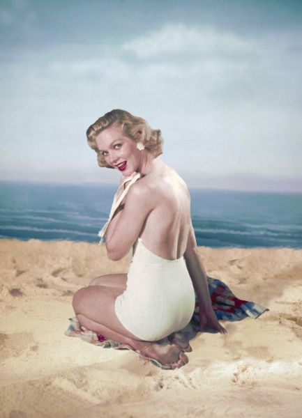 Fifties blonde wears a backless, white one-piece bathing costume while sitting on a sandy beach