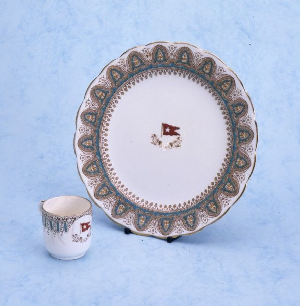 A cup and a plate bearing the White Star Line name and flag. Date: early 20th century