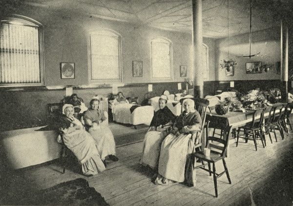 An old women's ward in the Whitechapel Workhouse Infirmary on Charles Street (later Baker's Row, now Vallance Road), East London. Some inmates lie in bed while other sit on chairs wearing the workhouse uniform of long dress, apron, shawl and bonnet