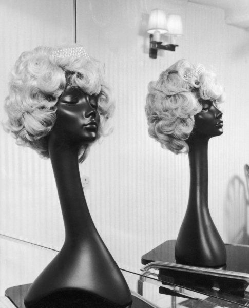 A blonde curly wig on a dummy with a tiara in a hairdresser's