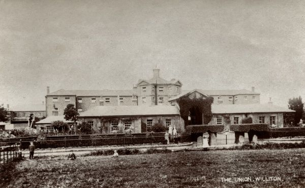 The Union workhouse at Williton, Somerset. Some of the workhouse staff and some local residents are visible. The building, designed by George Gilbert Scott and William Bonython Moffatt, opened in 1839. Date: Date unknown