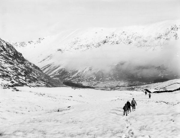 Ramblers trudging through the winter snow and mist in the Troutbeck Valley, Cumbria, England. Date: 1950s
