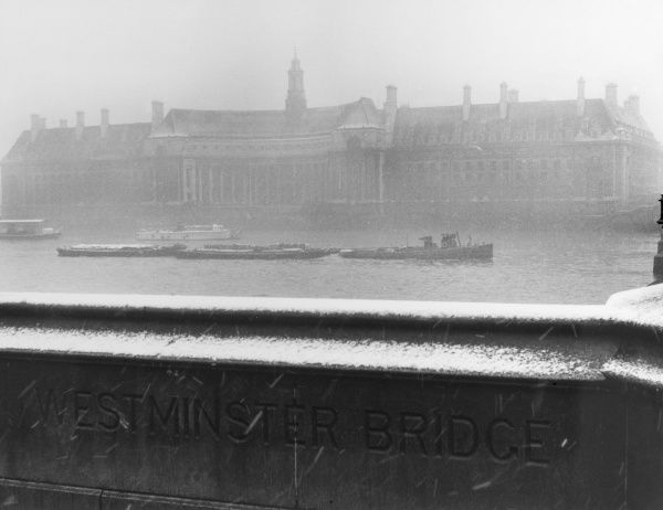 Winter in London : County Hall from Westminster Bridge during a snow storm. Date: 1960s