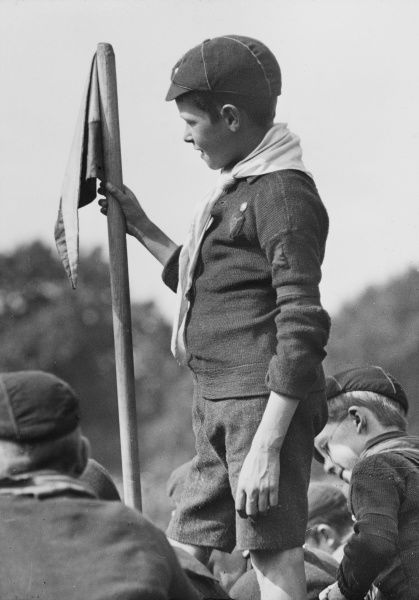 A wolf cub scout stands holding a flag at a scouting gathering at Hyde Park London held in the presence of Sir Robert Stephenson Smyth Baden Powell 1857-1941, founder of the Boy Scout movement and the Duke of York (later King George VI)