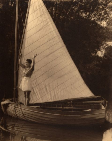 A woman stands and waves in front of the outstretched sail on a boat, on the Norfolk Broads in the 1930s