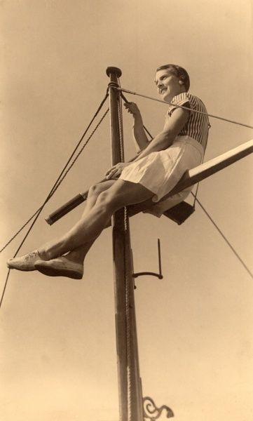 A woman in a natty nautical outfit of white shorts, plimsolls and striped blouse perches confidently high up on a boat's mast or yard arm during the 1930s