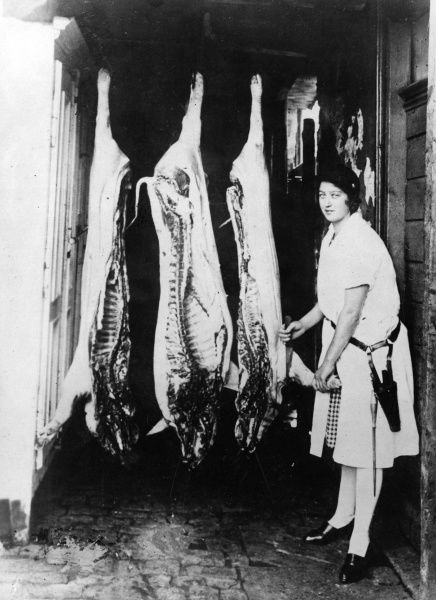 A young British female butcher proudly displays her freshly slaughtered pigs, hanging from their hooks. Date: 1920s