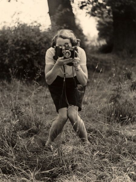 A woman with a camera adopts a photographer's pose for - another photographer