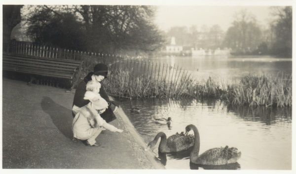 A woman and two children feeding swans and ducks in a London park. The woman is wearing a fashionable cloche hat and a coat with a fur collar