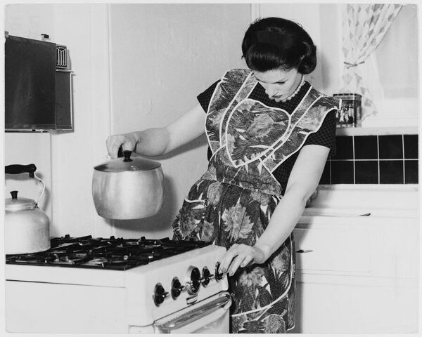 A woman in an apron holds a saucepan ready over the hob as she turns it
