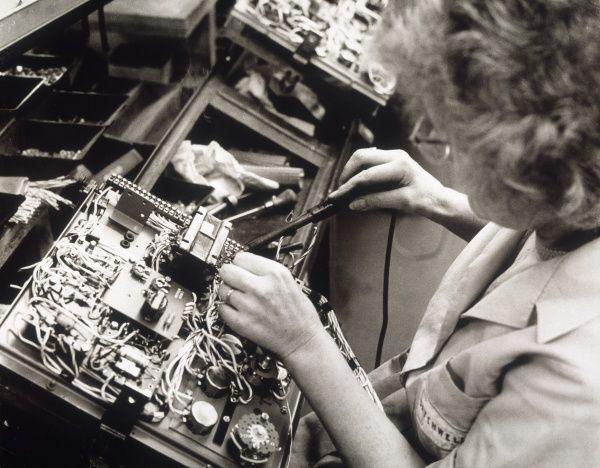 A female factory worker works on an automatic control for an air conditioning system