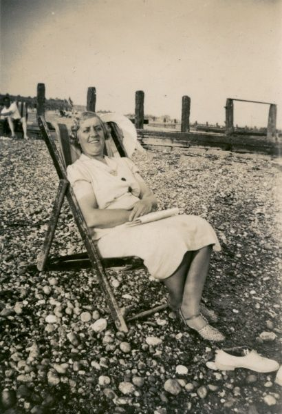 A woman on holiday, sitting in a deckchair on a pebbly beach.  circa 1930s