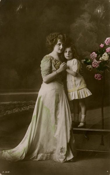 A woman in a full-length dress posing with a little girl, with a display of roses on the right, in a studio photo. Date: early 20th century