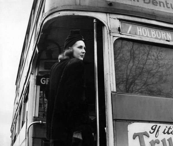 A woman in a stylish coat and turban style hat climbing aboard the no. 7 Routemaster London bus which is destined for Holborn by the looks of things. 1940s