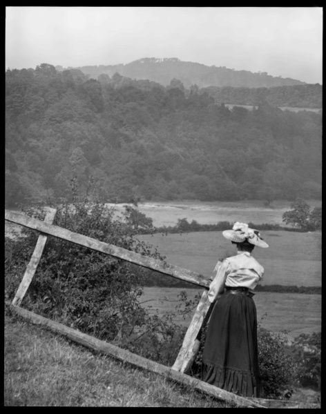 An Edwardian woman looking across fields, with trees and hills in the distance