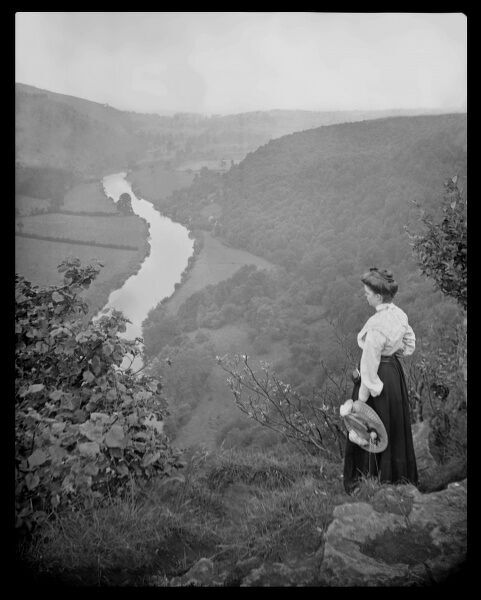 An Edwardian woman looking down into a valley between rolling hills, where a stream is flowing