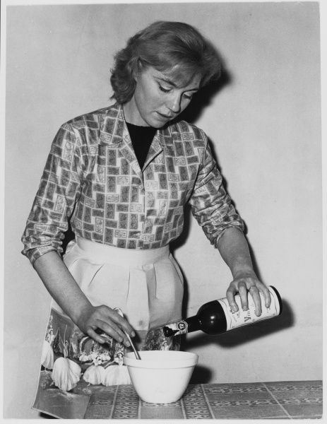 A woman pours wine into a mixing bowl, perhaps in preparation for making a sauce of some kind