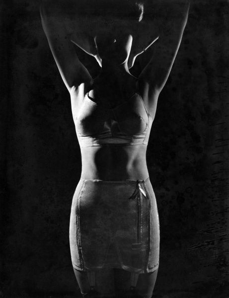 A woman modelling underwear (brassiere, corset, suspenders and stockings) in a shadowy, atmospheric photo.  circa 1940s