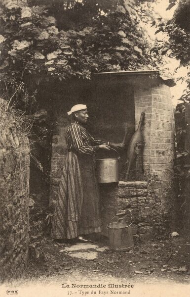 A woman from Normandy, France collecting a bucket of water at a well. A yolk rests against the brick surround of the well. Date: circa 1910s