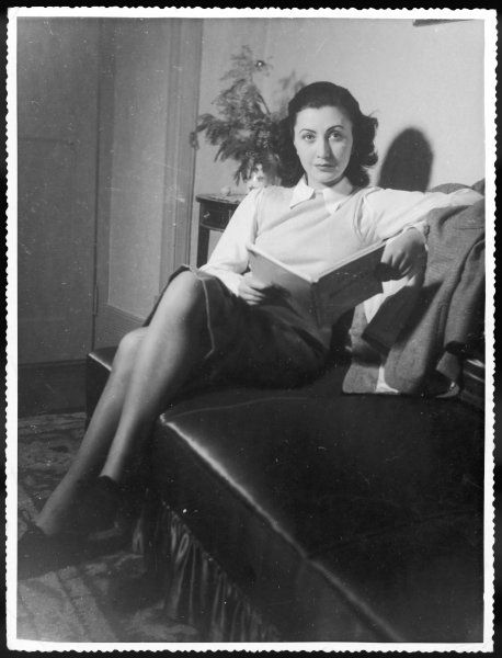 An elegant young woman reads whilst sitting on a settee at home
