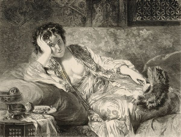 A rather annoyed looking young woman reclines on a couch, deep in thought