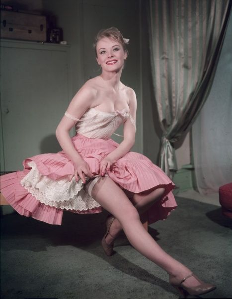 A woman reveals her garter from under her full pink skirt and white petticoat