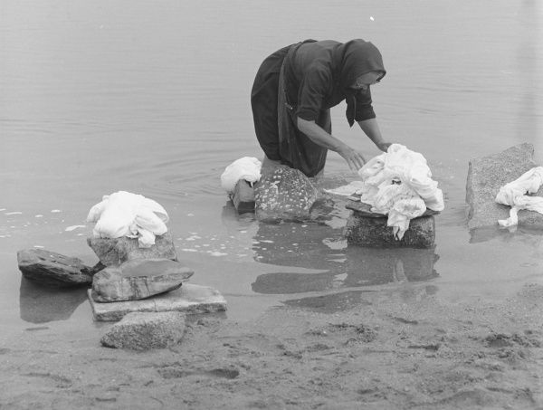 A woman standing knee deep in a river, sorting out items for washing which she has placed on various rocks