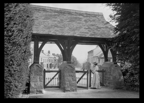 An Edwardian woman standing at a roofed gate with old stone pillars, perhaps leading from the church to the village