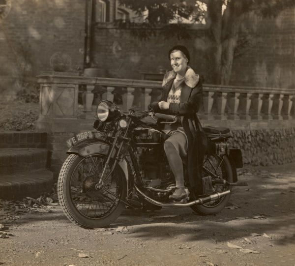 A lady sits astride a Super Sunbeam motorcycle outside the Red House in Buntingford, Hertfordshire, smiling and wearing a beret style hat, a fur-collared coat and Fair Isle jumper