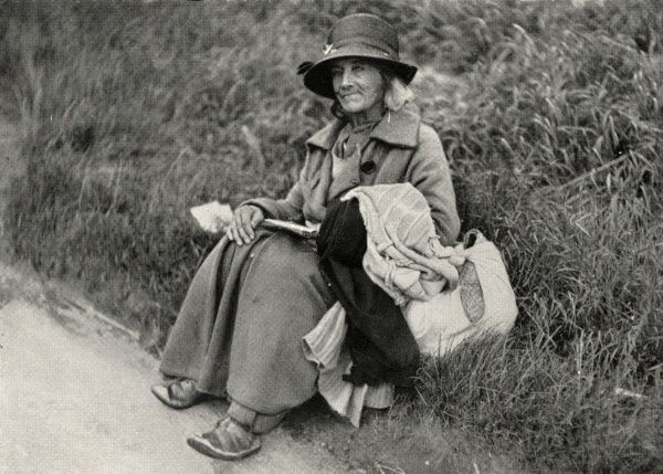 A female tramp, her skin tanned by the outdoor life, sits by the road, her bag of possessions at her side. Although her body is well wrapped in overcoat and hat, her feet are in open sandals