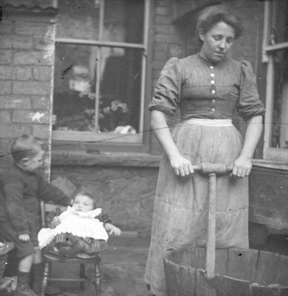 A woman using a dolly tub to do the weekly wash, in a back yard in South Wales, with two children on the left